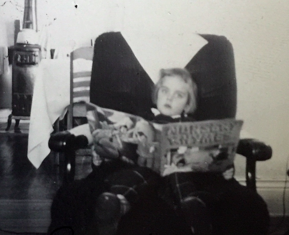 child reading a large book
